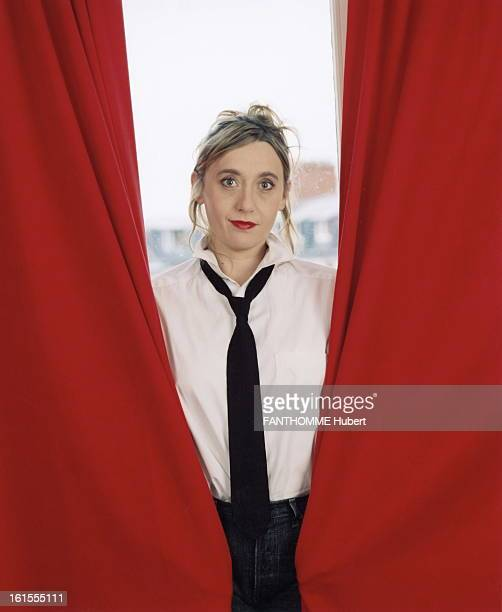 Rendezvous With Virginia Despentes Virginia DESPENTES smiling attitude white shirt and black tie posing between red curtains in PARIS
