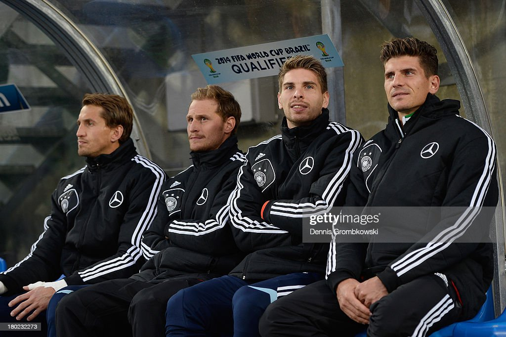 Rene Adler of Germany and teammates Benedikt Hoewedes, Ron-Robert Zieler and Mario Gomez sit on the bench prior to the FIFA 2014 World Cup Qualifier match between Faeroe Islands and Germany on September 10, 2013 in Torshavn, Denmark.