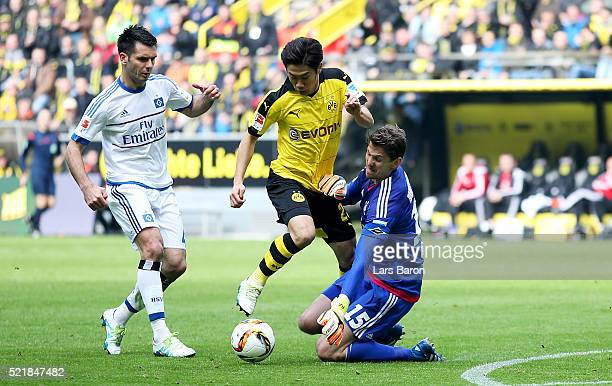 Rene Adler of Hamburg tackles Shinji Kagawa of Dortmund during the Bundesliga match between Borussia Dortmund and Hamburger SV at Signal Iduna Park...