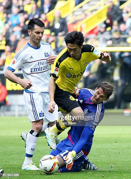 Rene Adler of Hamburg tackles Shinji Kagawa of Dortmund during the Bundesliga match between Borussia Dortmund and Hamburger SV at Signal Iduna Park...