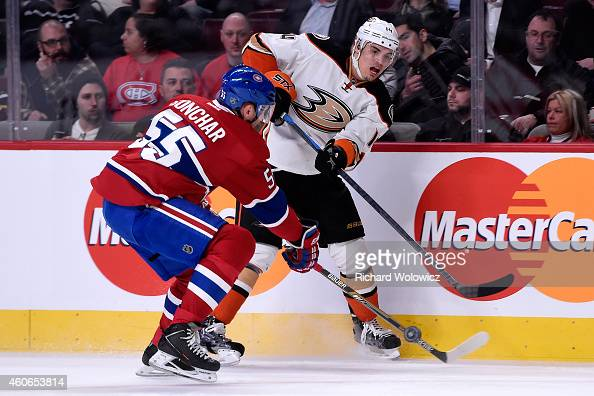 Rene Bourque of the Anaheim Ducks passes the puck in front of Sergei Gonchar of the Montreal Canadiens during the NHL game at the Bell Centre on...