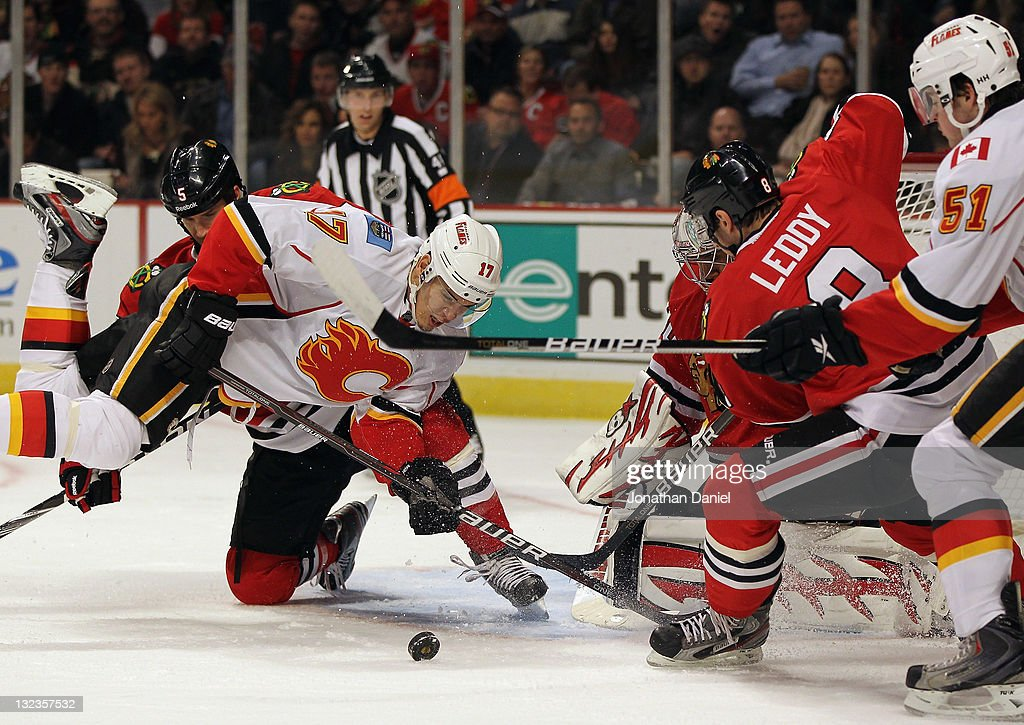<a gi-track='captionPersonalityLinkClicked' href=/galleries/search?phrase=Rene+Bourque&family=editorial&specificpeople=685715 ng-click='$event.stopPropagation()'>Rene Bourque</a> #17 of the Calgary Flames falls trying to shoot the puck against <a gi-track='captionPersonalityLinkClicked' href=/galleries/search?phrase=Ray+Emery&family=editorial&specificpeople=218109 ng-click='$event.stopPropagation()'>Ray Emery</a> #30 and <a gi-track='captionPersonalityLinkClicked' href=/galleries/search?phrase=Nick+Leddy&family=editorial&specificpeople=5894600 ng-click='$event.stopPropagation()'>Nick Leddy</a> #8 of the Chicago Blackhawks at the United Center on November 11, 2011 in Chicago, Illinois.