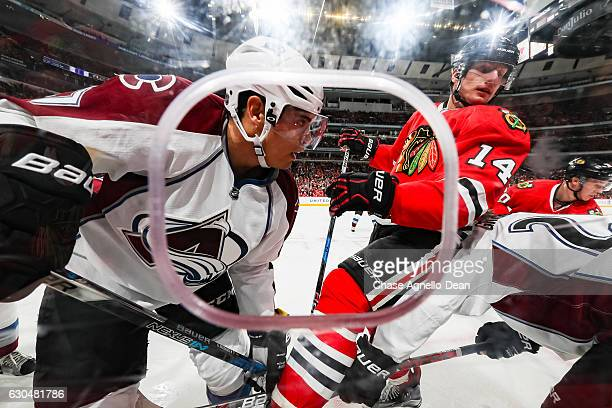 Rene Bourque of the Colorado Avalanche and Richard Panik of the Chicago Blackhawks work to get at the puck by the boards in the second period at the...