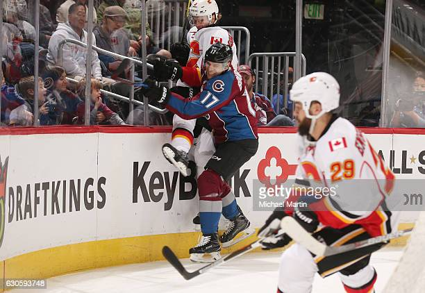 Rene Bourque of the Colorado Avalanche checks Jyrki Jokipakka of the Calgary Flames into the glass at the Pepsi Center on December 27 2016 in Denver...