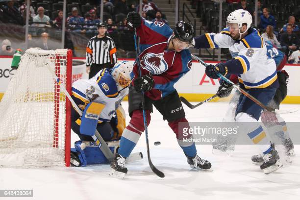 Rene Bourque of the Colorado Avalanche deflects a puck between his legs towards goaltender Jake Allen of the St Louis Blues at the Pepsi Center on...