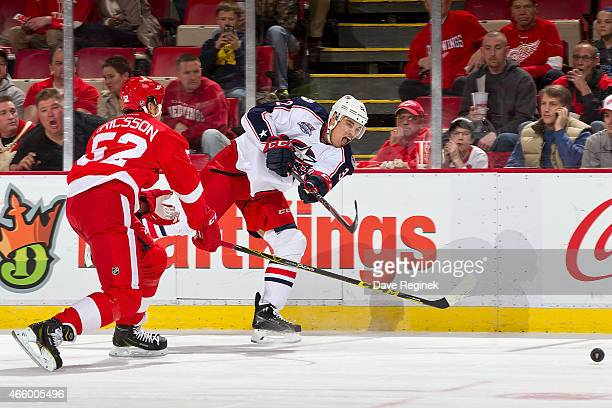 Rene Bourque of the Columbus Blue Jackets shoots the puck as Jonathan Ericsson of the Detroit Red Wings pressures him during a NHL game on March 12...