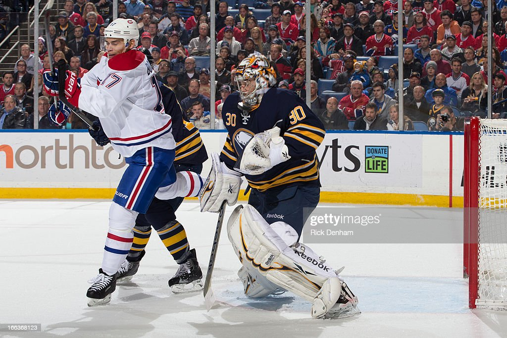 Rene Bourque #17 of the Montreal Canadiens and Ryan Miller #30 of the Buffalo Sabres keep an eye on a high shot during the NHL game at First Niagara Center on April 11, 2013 in Buffalo, New York.