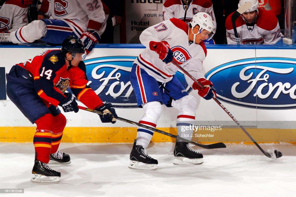 Rene Bourque #17 of the Montreal Canadiens digs the puck out from the boards against Tomas Fleischmann #14 of the Florida Panthers at the BB&T Center on February 14, 2013 in Sunrise, Florida.