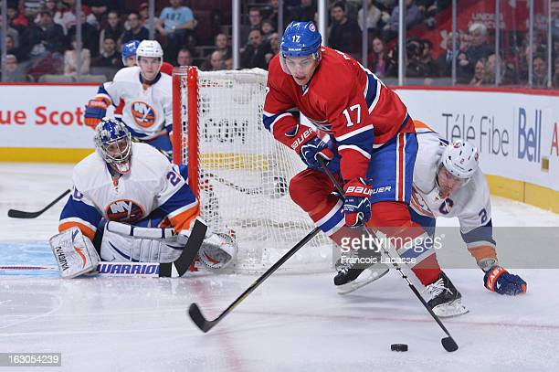 Rene Bourque of the Montreal Canadiens passes the puck against pressure from Mark Streit of the New York Islanders during an NHL game on February 21...