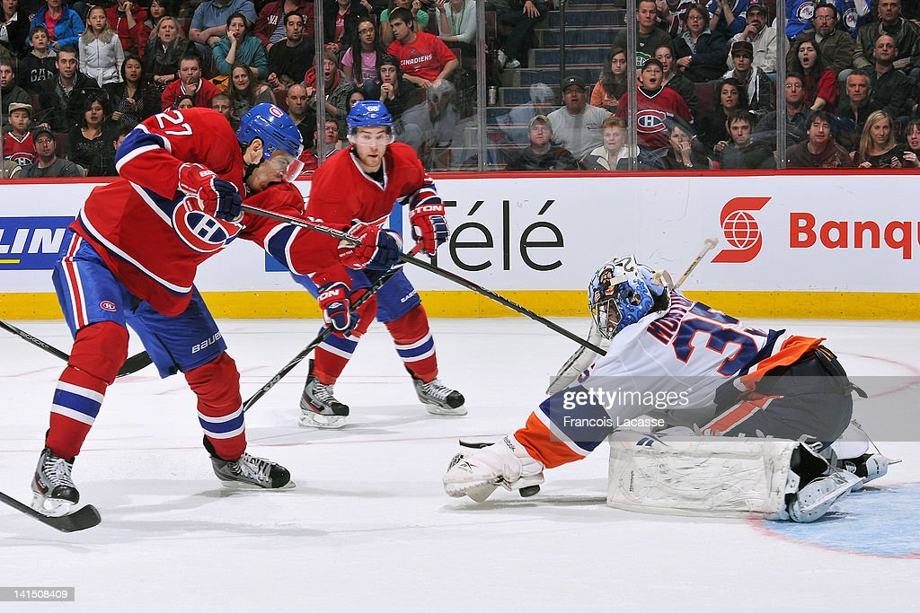 <a gi-track='captionPersonalityLinkClicked' href=/galleries/search?phrase=Rene+Bourque&family=editorial&specificpeople=685715 ng-click='$event.stopPropagation()'>Rene Bourque</a> #27 of the Montreal Canadiens takes a shot on goalie <a gi-track='captionPersonalityLinkClicked' href=/galleries/search?phrase=Al+Montoya&family=editorial&specificpeople=213916 ng-click='$event.stopPropagation()'>Al Montoya</a> #35 of the New York Islanders as <a gi-track='captionPersonalityLinkClicked' href=/galleries/search?phrase=Yannick+Weber&family=editorial&specificpeople=4324944 ng-click='$event.stopPropagation()'>Yannick Weber</a> #68 follows the play during the NHL game on March 17, 2012 at the Bell Centre in Montreal, Quebec, Canada.