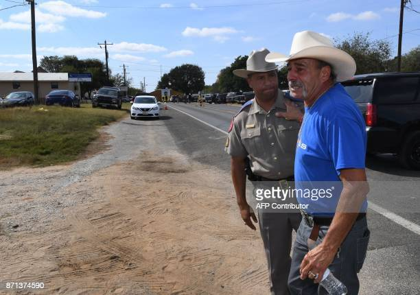 Rene Morino hugs a state trooper at a memorial outside the First Baptist Church after a mass shooting that killed 26 people in Sutherland Springs...