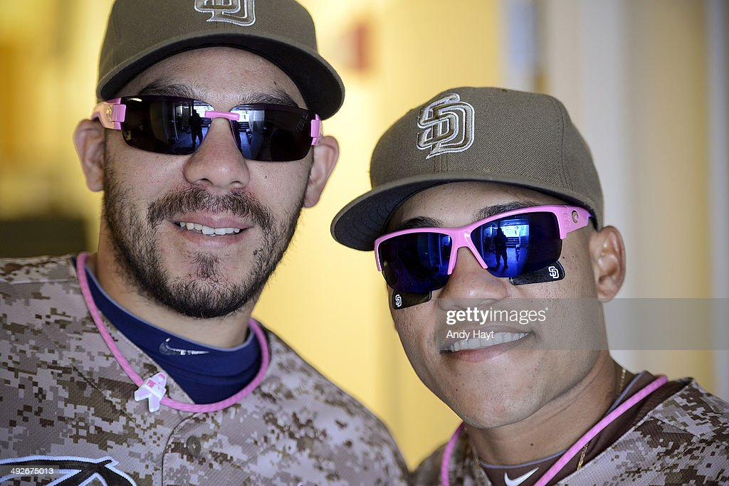 Rene Rivera and Alexi Amarista of the San Diego Padres pose for a photo showing Mothers Day uniform accessories prior to the game against the Miami...