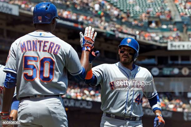 Rene Rivera of the New York Mets is congratulated by Rafael Montero after hitting a two run home run against the San Francisco Giants during the...