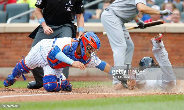 Rene Rivera of the New York Mets is late with the tag as Anthony Rendon of the Washington Nationals scores a run in the third inning at Citi Field on...