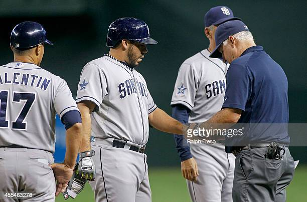 Rene Rivera of the San Diego Padres has his hand examined by the team trainer after being hit by a pitch against the Arizona Diamondbacks as first...
