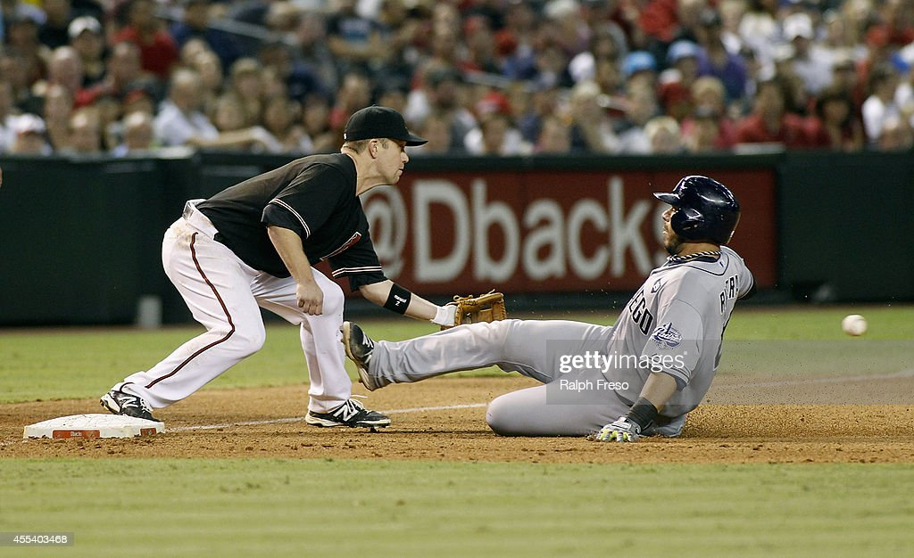 Rene Rivera #44 of the San Diego Padres slides into third base with a triple as Aaron Hill #2 of the Arizona Diamondbacks fields the throw during the sixth inning of a MLB game at Chase Field on September 13, 2014 in Phoenix, Arizona.