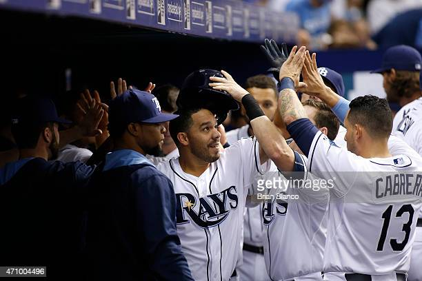 Rene Rivera of the Tampa Bay Rays celebrates with teammates including Asdrubal Cabrera in the dugout following his tworun home run during the fourth...