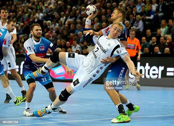 Rene Toft Hansen of Kiel challenges for the ball with Niklas Russ and Fabian Boehm of BalingenWeilstetten during the DKB HBL Bundesliga match between...