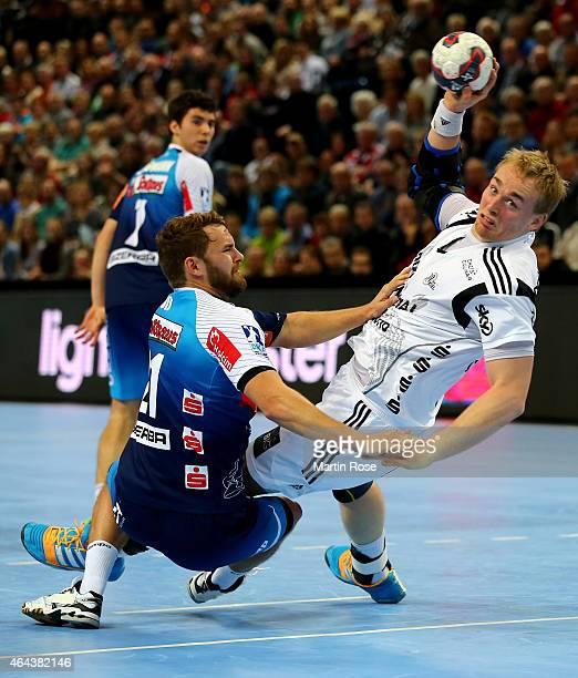 Rene Toft Hansen of Kiel challenges for the ball with Niklas Russ of BalingenWeilstetten during the DKB HBL Bundesliga match between THW Kiel and...