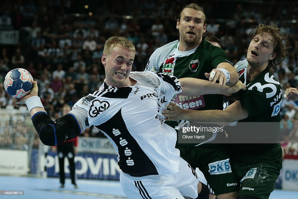 Rene Toft Hansen (L) of Kiel challenges for the ball with Pavel Horak (C) and Jesper Nielsen (R) of Berlin during the DKB HBL Bundesliga match between THW Kiel and Fuechse Berlin on May 24, 2014 in Kiel, Germany.
