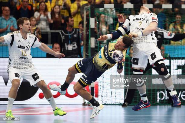 Rene Toft Hansen of Kiel fouls Alexander Petersson of RheinNeckar Loewen during the EHF Champions League Quarter Final Leg 2 match between Rhein...