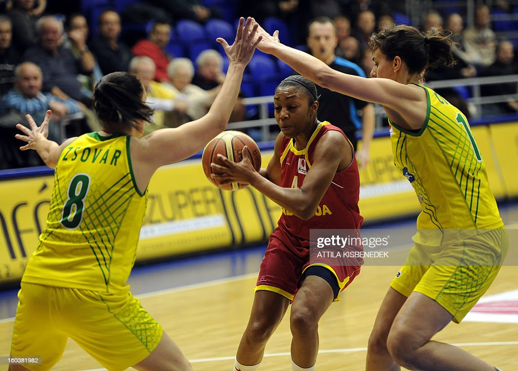 Renee Montgomery (C) of Russian Nadezhda Orenburg fights for the ball with Hungarian Reka Cserny (R) and Orsolya Zsovar (L) of Hungarian UE Sopron on January 30, 2013 during their basketball EuroLeague match in Sopron, Hungary.