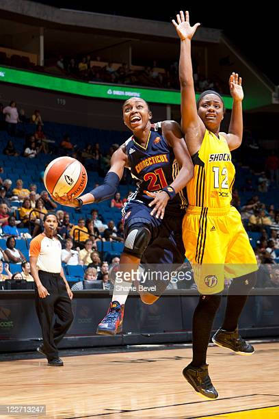 Renee Montgomery of the Connecticut Sun drives past Ivory Latta of the Tulsa Shock during the WNBA game on August 28 2011 at the BOK Center in Tulsa...