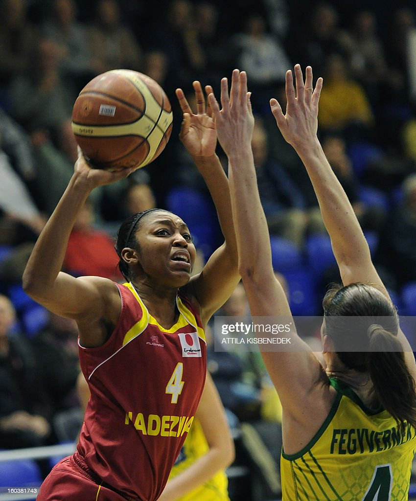 Renee Montomery (L) of Russian Nadezhda Orenburg scores a basket against Hungarian Zsofia Fegyverneky (R) of Hungarian UE Sopron in the locak sport hall on January 30, 2013 during their basketball EuroLeague match in Sopron, Hungary. AFP PHOTO / ATTILA KISBENEDEK