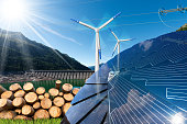 Renewable energies sources - Wind energy (wind turbines),  solar energy (solar panels), biomass (tree trunks) and hydropower (dam for hydroelectric power)