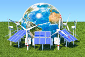 Renewable energy concept. Solar panels and wind turbines around the Earth Globe in the green grass against blue sky. The source of the map - https://svs.gsfc.nasa.gov/3615
