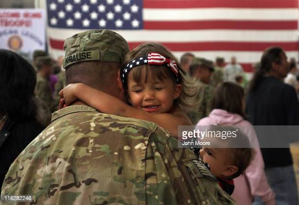 Reniah Krause clings to her father Sgt Joseph Krause after he and fellow soldiers arrived from Afghanistan on June 15 2011 to Fort Carson Colorado...