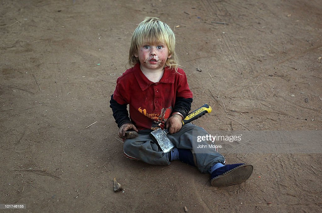 Renier Christian plays with a hatchet while sitting in the dirt of a White South African squatter camp on June 7 2010 in Krugersdorp South Africa The...