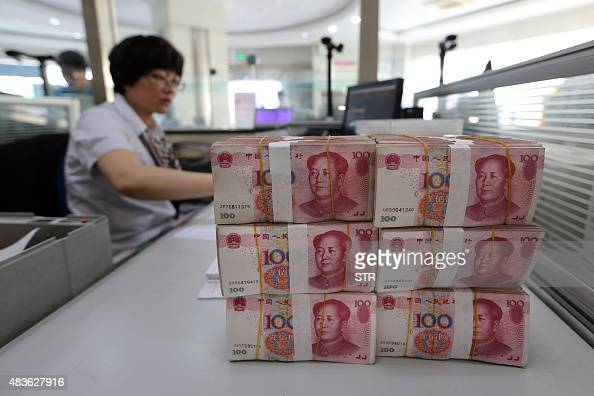 Renminbi banknotes are placed on a bank staff's table in a bank in Lianyungang east China's Jiangsu province on August 11 2015 China's central bank...