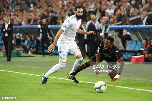 Rennes' Congolese forward Firrmin Mubele Ndombe falls in front of Marseille's French defender Adil Rami during the French L1 football match Olympique...