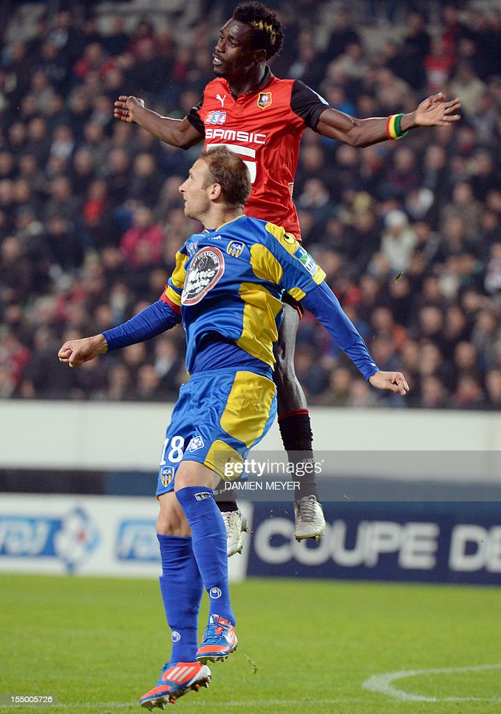 Rennes' defender John Boye (top) of Ghana fights for the ball with Arles Avignon striker David Suarez during the French League Cup football match Rennes against Avignon on October 30 , 2012 at the route de Lorient stadium in Rennes, western France.