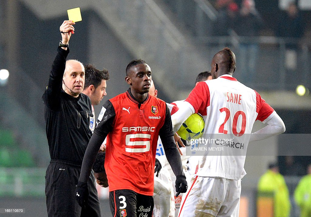 Rennes' French defender Chris Mavinga (C) receives a yellow card from French referee Jean Charles Cailleux during the French L1 football match Rennes vs Nancy on March 30, 2013 at the Route de Lorient stadium in Rennes, western France.
