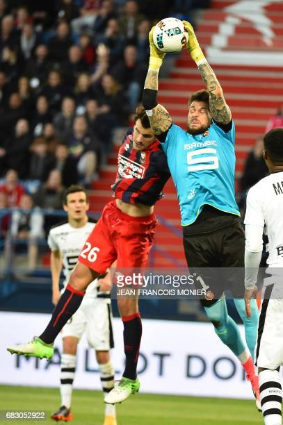 Rennes' French goalkeeper Benoit Costil makes a save in front of Caen's Croatian forward Ivan Santini during the French L1 football match between...