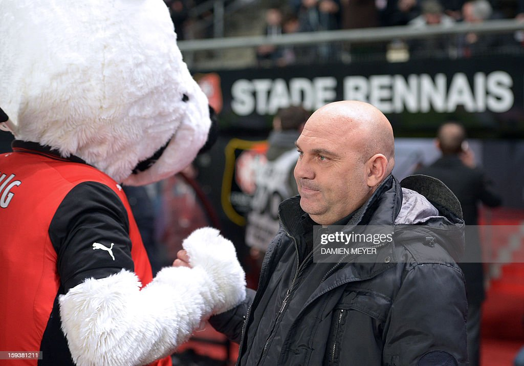 Rennes' French head coach Frederic Antonetti shakes hands with Rennes' mascot during a French L1 football match between Rennes and Bordeaux on January 12, 2013 at the route de Lorient stadium in Rennes, western France.