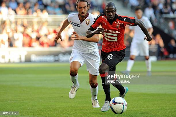 Rennes' French midfielder Abdoulaye Doucoure runs with the ball in front of Torino's Italian defender Emiliano Moretti during the friendly football...
