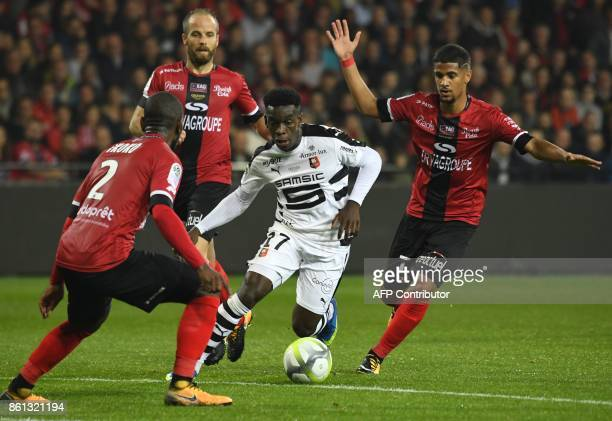 Rennes' French midfielder Faitout Maouassa vies with Guingamp's FranchCongolese defender Jordan Ikoko and Guingamp's French midfielder Ludovic Blas...