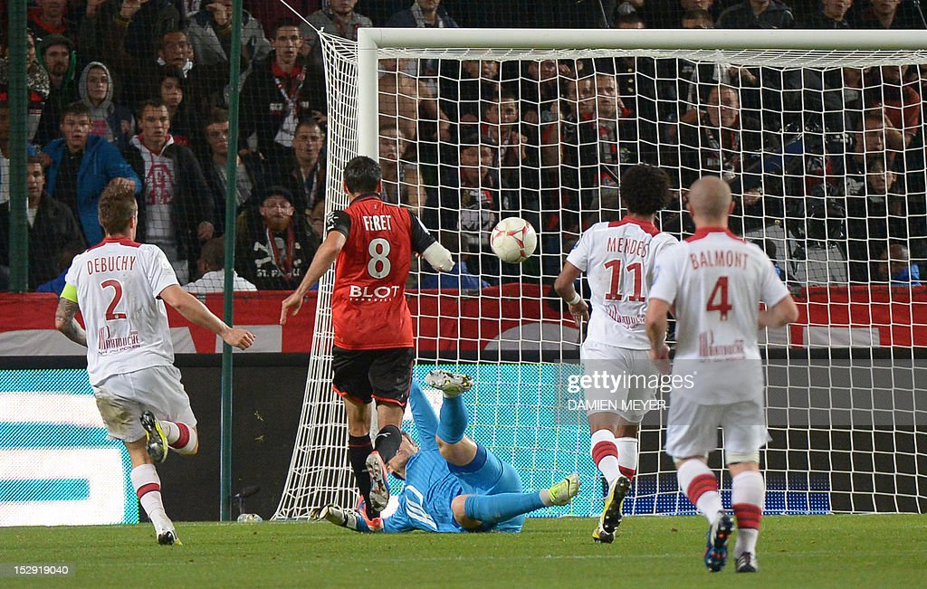 Rennes' French midfielder Julien Feret (C) scores a goal defeating Lille's French goalkeeper Mickael Landreauduring the French L1 football match Stade Rennais FC vs Lille LOSC, on September 28, 2012, at the route de Lorient stadium in Rennes, western France.