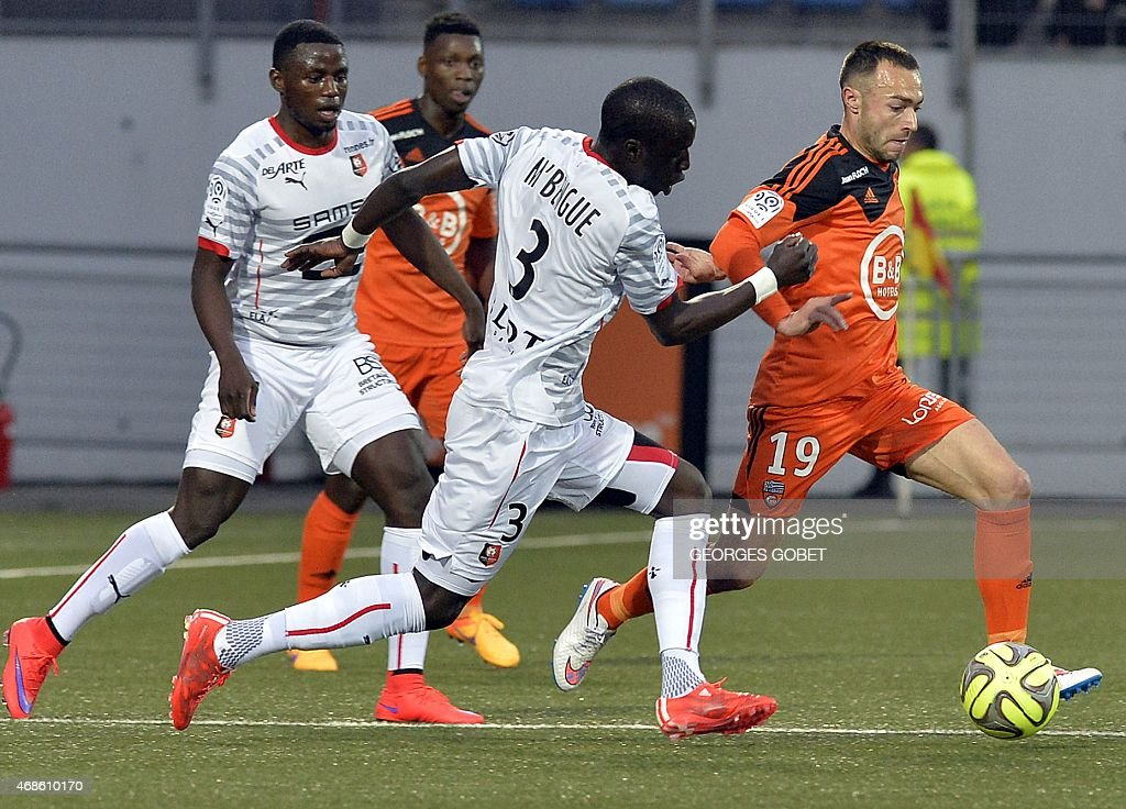 Rennes' French Senegalese defender Cheik Mbengue (C) and Lorient's French midfielder Romain Philippoteaux fight for the ball during the French L1 football match between FC Lorient and Stade Rennais FC on April 4, 2015 at the Stade du Moustoir. AFP PHOTO / GEORGES GOBET