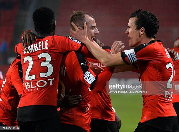 Rennes' Polish forward Kamil Grosicki is congratulated by his teammates Rennes' French forward Ousmane Dembele and Rennes' French defender Romain...