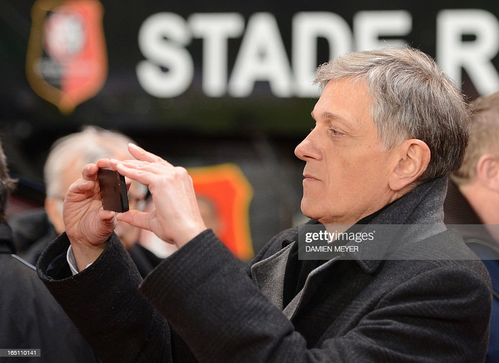 Rennes' president Frederic de Saint-Sernin takes a picture with his mobile phone before the French L1 football match Rennes vs Nancy on March 30, 2013 at the Route de Lorient stadium in Rennes, western France. AFP PHOTO / DAMIEN MEYER