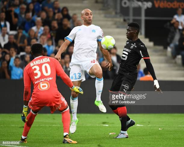 Rennes' Senegalese forward Ismaila Sarr vies with Marseille's Tunisian defender Aymen Abdennour and French goalkeeper Steve Mandanda during the...