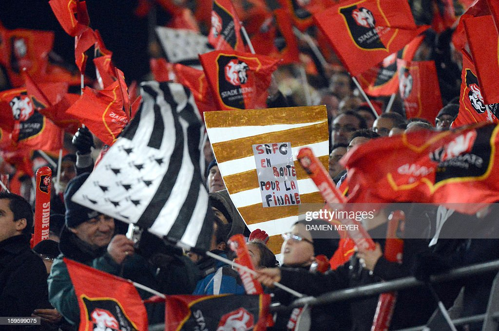 Rennes' supporters celebrate with a fake cup after Rennes won 2-0 a French League Cup semifinal football match between Rennes and Montpellier on January 16, 2013 at the route de Lorient stadium in Rennes, western France.