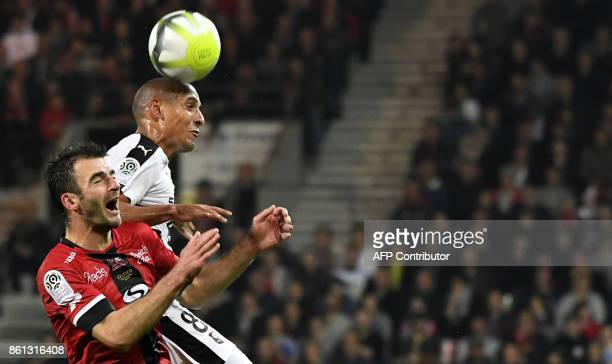 Rennes' Tunisian midfielder Wahbi Khazri heads the ball next to Guingamp's French midfielder Christophe Kerbrat during the French Ligue 1 football...