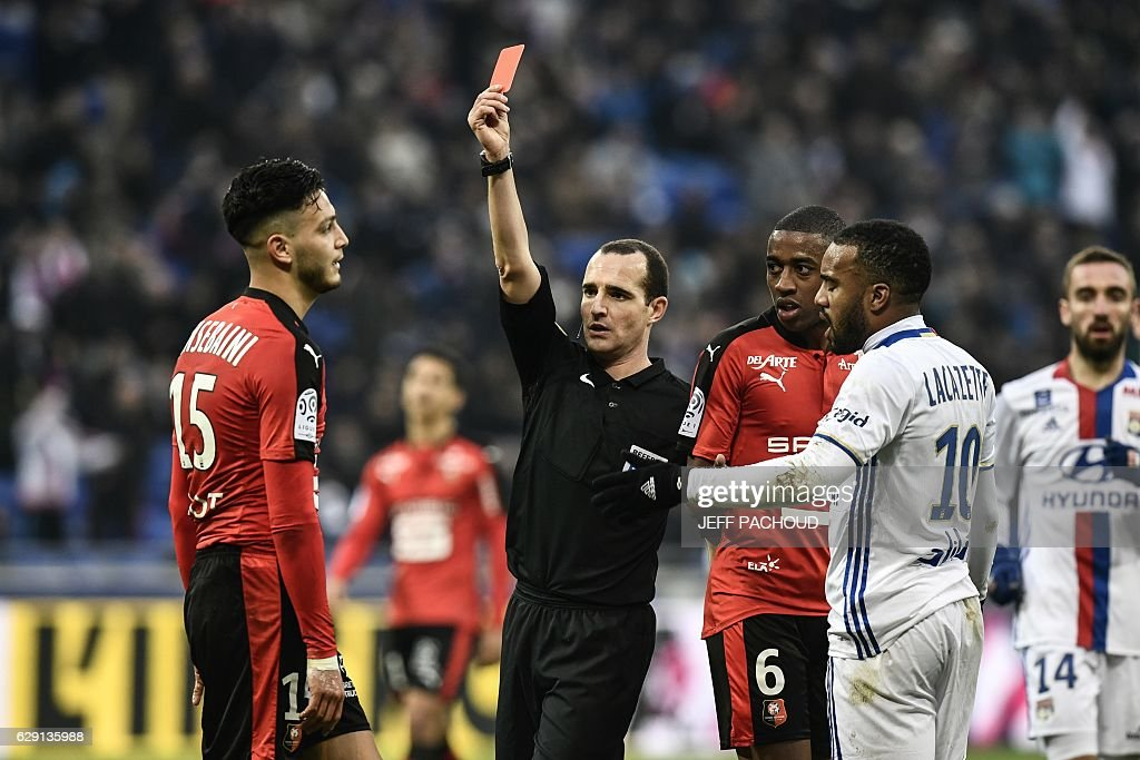 Rennes'Algeria defender Ramy Bensebaini (L) receives a red card from French referee Benoit Millot (C) during the French L1 football match Olympique Lyonnais (OL) vs Rennes (Stade Rennais) on December 11, 2016, at the Parc Olympique Lyonnais stadium in Decines-Charpieu, central-eastern France. / AFP / JEFF