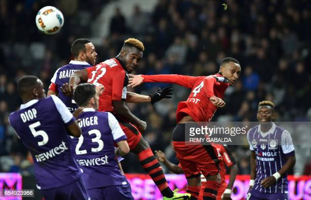 Rennes's defender Joris Gnagnon and Rennes's Mozambican defender Mexer go for a header during the French L1 football match Toulouse vs Rennes on...