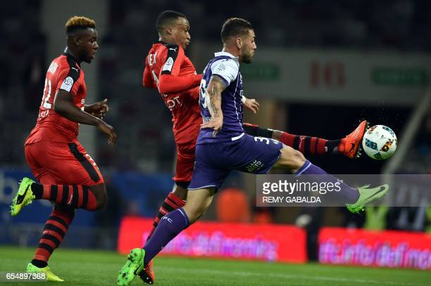 Rennes's Mozambican defender Mexer vies with Toulouse's French forward Andy Delort during the French L1 football match Toulouse vs Rennes on March 18...
